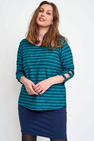 The model in this photo is wearing a Pont Neuf Melly top. A textured wave fabric in fabulous petrol and navy available in sizes 14-30 from Bakou